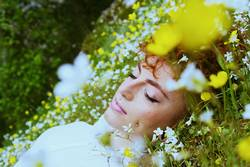 Young woman sleeping in a field of flowers