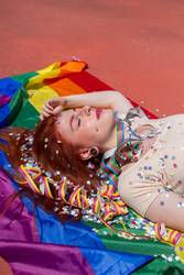 Young woman lying down over a rainbow flag
