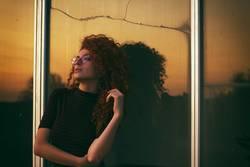 Junge Frau mit dem Sonnenuntergang als Hintergrund