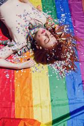 Young woman sleeping over a rainbow flag
