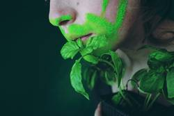 Close up of a young woman's mouth and a plant