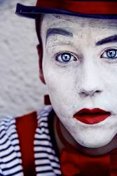 Young man with clown make up and blue eyes