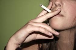 Junge Frau mit Zigarette vor grünem Hintergrund
