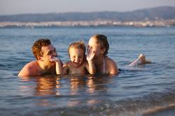 Laughing little boy with his parents at the sea