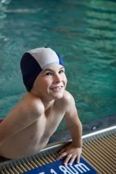 Fröhlicher kleiner Junge im Schwimmbad mit Badekappe