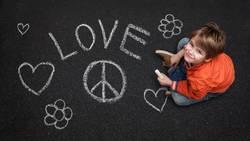 Junge mit Kreide will Frieden und Liebe