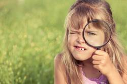 Happy little girl exploring nature with magnifying glass