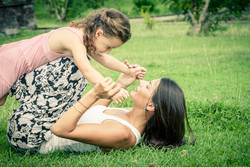 Happy mother and daughter playing in the park