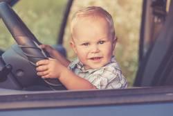 One little boy sitting in the car