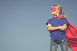 Glückliches kleines Kind, das Superhelden spielt.