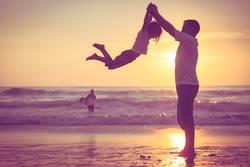 Vater und Sohn, die auf dem Strand zur Sonnenuntergangzeit spielen.