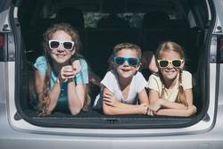 Happy brother and his two sisters are sitting in the car.