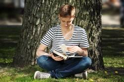 Teen boy reading a book