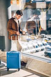 Man with smartphone and suitcase