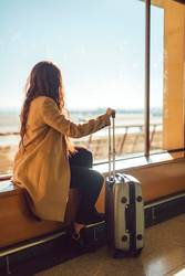 Unrecognizable woman at window in airport