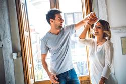 Cheerful young couple dancing in sun light