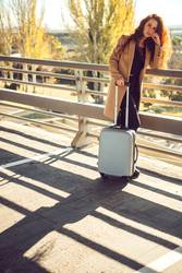 Redhead girl with suitcase in sunlight