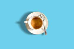 minimalist top view of a coffee cup on a light blue pastel table