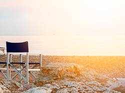 empty folding outdoor chair on a pebble beach