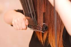 Frau trocknete ihr Haar mit Pinsel und Fön