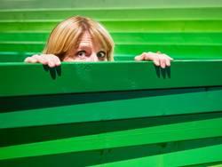 Junge Frau schaut vorsichtig über einen Holzzaun