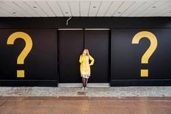 junge Frau mit gelber Regenjacke zwischen zwei Fragezichen
