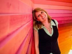 junge Frau lehnt glücklich an einer bunten Holzwand