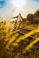 junge Frau balanciert auf Schienen im Sonnenuntergang