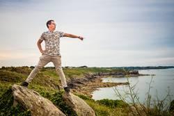 Mann auf Fels zeigt aufs Meer