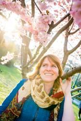 junge Frau unter einem Baum mit Kirschblüten