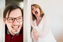 Mann schaut durch Türspalt und Frau hat Angst hinter der Tür