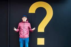 Junger Mann mit Regenjacke neben einem gelben Fragezeichen