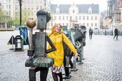 junge Frau in gelber Regenjacke marschiert mit