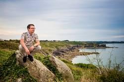 Mann hockt auf Fels an der Küste und schaut aufs Meer