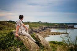Mann sitzt auf Fels an der Küste und schaut aufs Meer