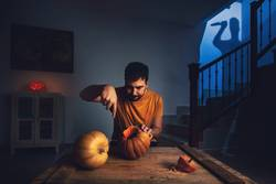 man cutting halloween pumpkin
