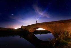 Man crossing bridge in the countryside at night