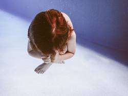 kauernder Junge unterwasser