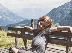 Junge sitzt auf Bank im Hintergrund die Berge