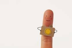 Witziger Finger-Fotograf mit kleiner Kamera aus Papier