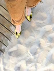 gelbschwarz karierte Slingpumps am Sandstrand