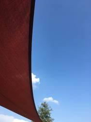 blauer Himmel mit Sonnensegelschutz