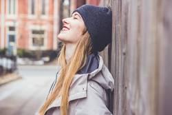 Junge Frau lehnt an Holzaun und ist glücklich