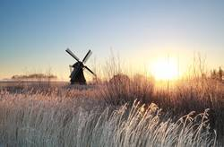 gold sunrise over Dutch windmill on frosty morning