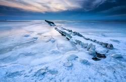frozen breakwater in ice on Ijsselmeer lake, Netherlands