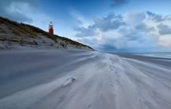 Leuchtturm an der Nordseeküste in der Abenddämmerung und starkem Wind