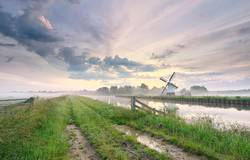 beautiful morning over charming windmill by river