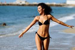 Young Arab woman in swimwear smiling on a tropical beach.