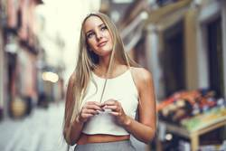 Beautiful young blonde woman in urban background.