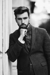 Young bearded man wearing british elegant suit